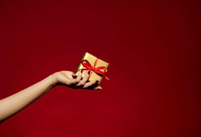A beautiful hand with long fingers holds a small gift wrapped in gold wrapping paper and tied with a red satin ribbon. Red background.