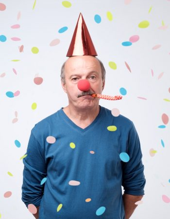Unhappy birthday senior man is sad and disappointed because nobody came to celebrate his anniversary. Blowing party horn, funny cap and red clown nose on him. confetti flying around him.