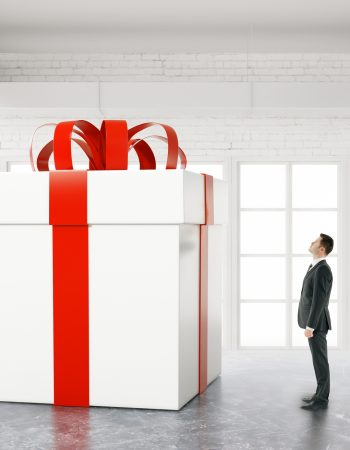 Businessman looking at huge present box in white brick interior. 3D Rendering